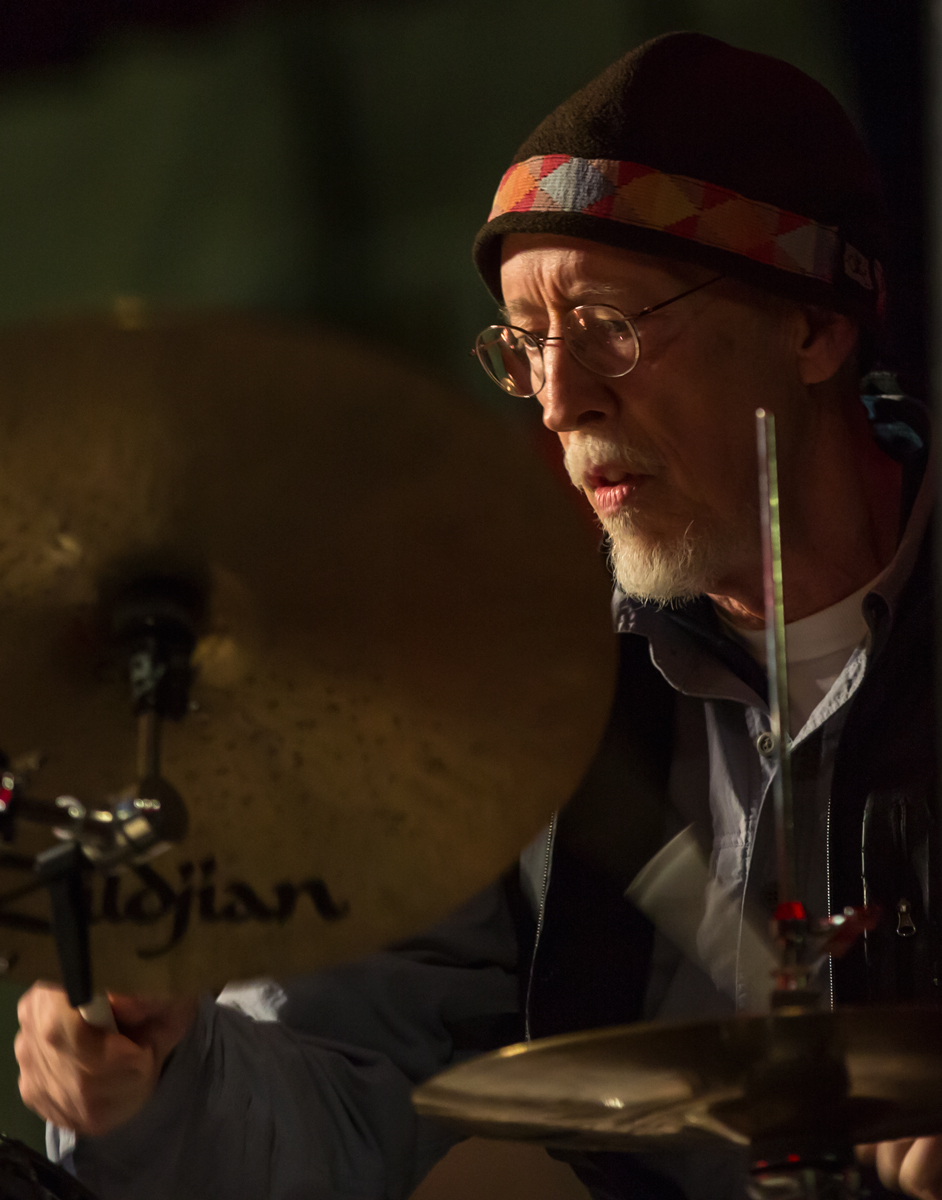 George Marsh 2016 This shows the intense concentration on George's face during a concert with the David Grisman Sextet. The colors and shapes surrounding his illuminated face and hands behind his cymbals are the basis of this composition.