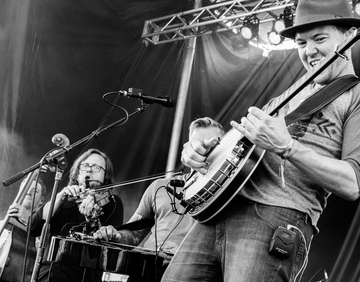 The Infamous Stringdusters at Green River Festival The Stringdusters feature two Berklee graduates, Chris Pandolfi on banjo and Andy Hall (partially hidden) on dobro. This shot was taken at the 2017 festival in Greenfield, Massachusetts. Chris's expression combined with the tilt of the image tries to capture the intensity of the moment. I like photos of bands to give viewers the perspective of being on stage.