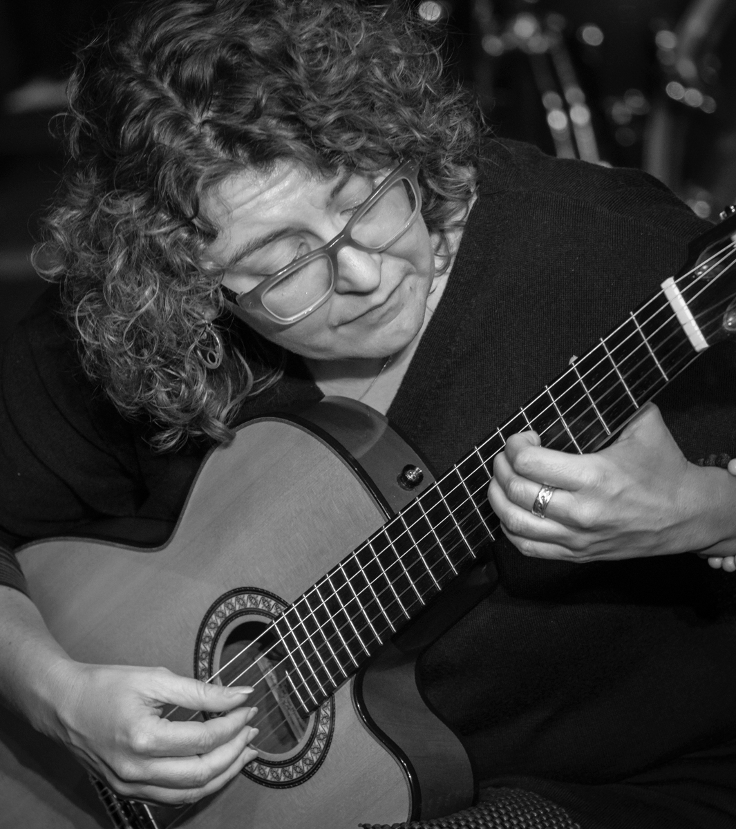 Kim Perlak 2018 Kim Perlak, Chair of the Guitar Department hunched over her guitar, the neck of her instrument dissects this frame diagonally. Kim's face and hands stand out against the neutral tones.