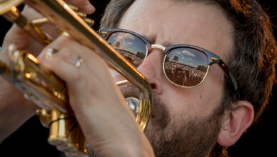 Matt Rubin with Dustbowl Revival 2017 Trumpeter Matt Ruben on stage at Green River Festival in Greenfield, MA. This closeup uses the reflections in his glasses to show both the audience and performer.