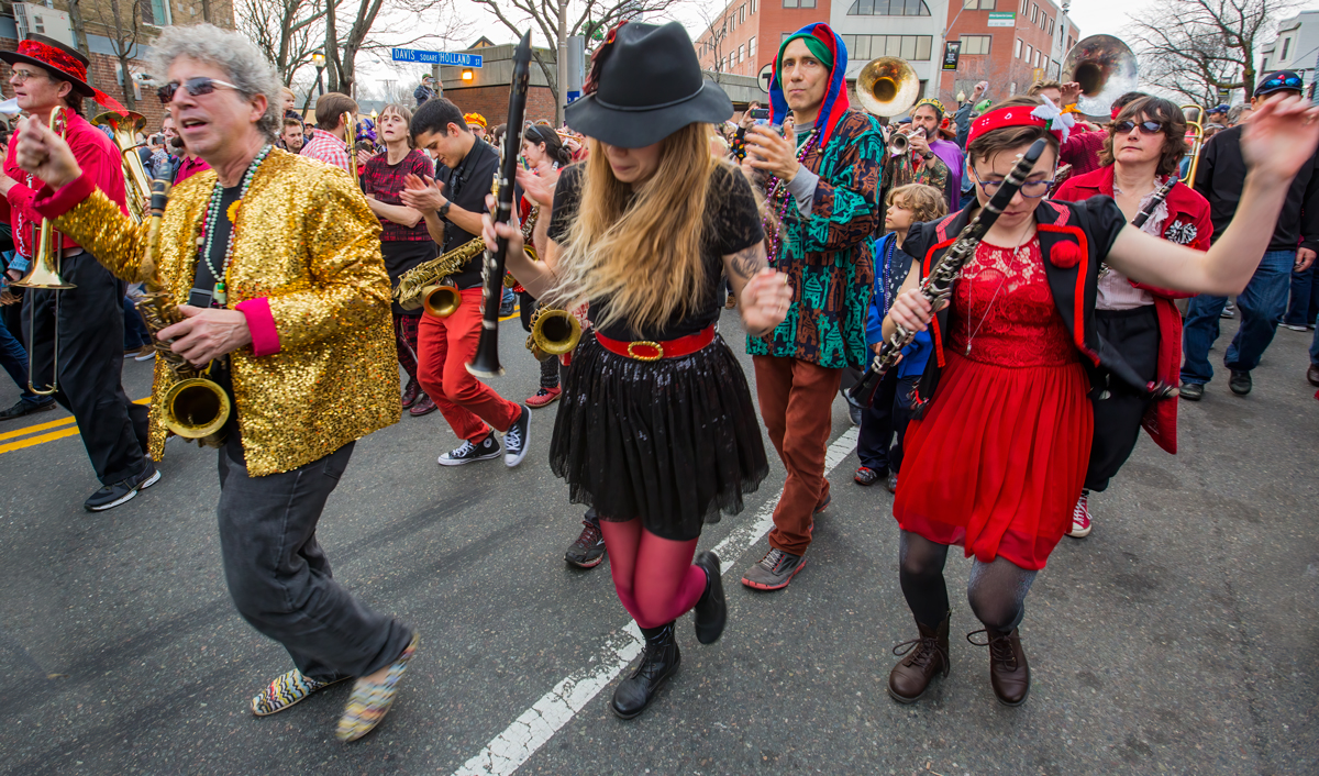 Revolutionary Snake Ensemble on parade in Davis Square 2016 Ken Field, in gold, leads his troupe down Holland Street, followed by people who came out to commemorate the closing of a 47-year institution of Boston's music scene, Johnny D's Uptown. Bright colors, motion blur and wide angle distortion reflect the festive spirit of day.