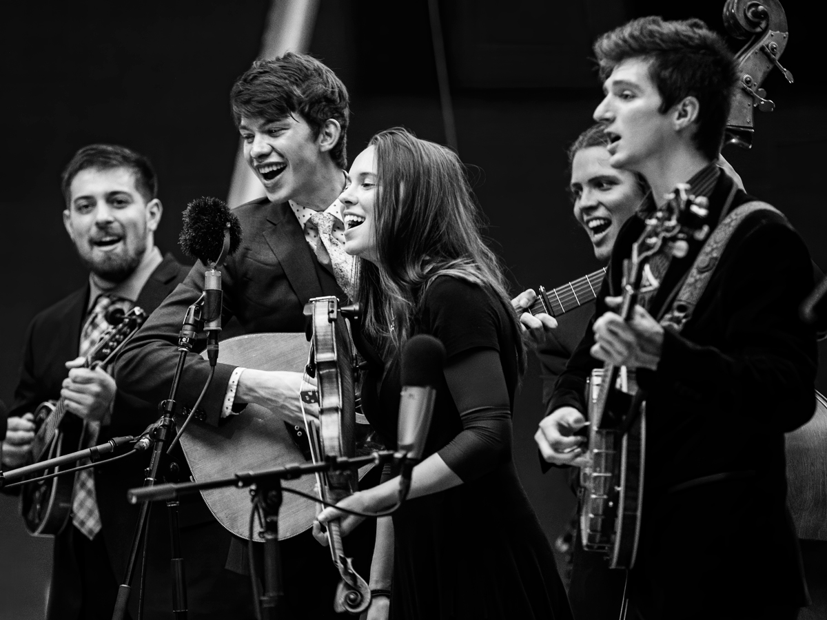 The Ruta Beggars 2019 A Berklee Bluegrass band was a hit at the 2019 International Bluegrass Association, World of Bluegrass convention in Raleigh, NC. Shooting from the side of the stage with a 200mm lens compresses the look of the photo and also helps avoid mics covering people's faces. The smiles on their faces speak to the joy they always bring to their shows.